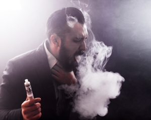 Man smoking e-cigarette, surrounded by a vape cloud, and coughing